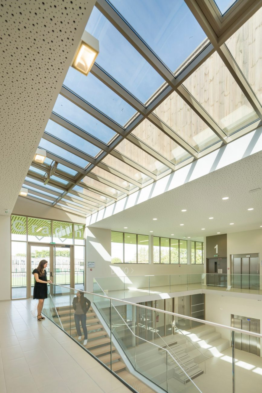 Double height sports center interior with glass balustrade
