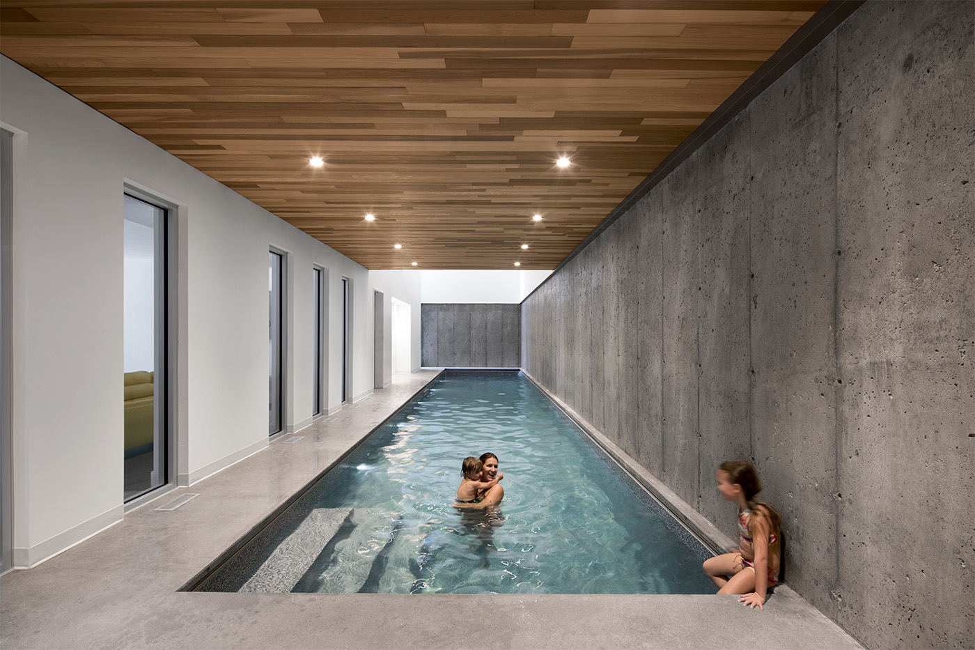 Indoor swimming pool with wooden roof and lighting